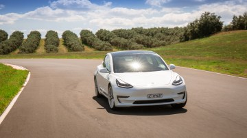 Drive Car of the Year Best Electric Vehicle 2021 finalist Tesla Model 3 driven on road front-on wide shot