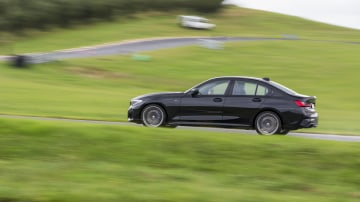 Drive Car of the Year Best Medium Luxury Car 2021 finalist BMW 3 Series wide shot on road against green grass