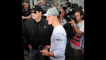 Michael Schumacher meets John Travolta before race.