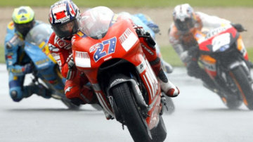 Casey Stoner (centre) claims his fifth victory of the season at the British MotoGP.
