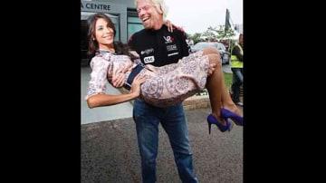 Sir Richard Branson sweeps Pia Miller off her feet.
