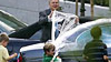 Karl Rove unwraps his car with the help of children. Photo: AFP
