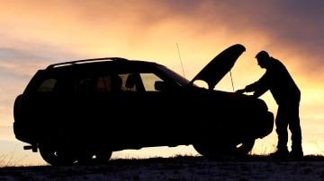 Silhouette of man checking under car bonnet