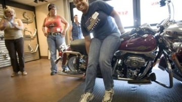 Potential buyers get acquainted with a female-friendly Harley-Davidson at a garage party in Texas, part of the motorcycle manufacturer's push to sell its machines to women. Picture: New York Times