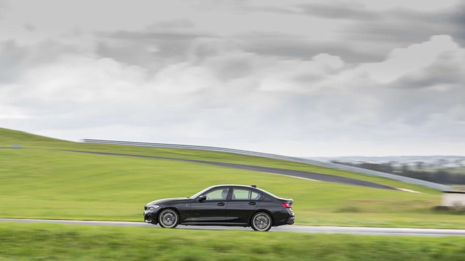Drive Car of the Year Best Medium Luxury Car 2021 finalist BMW 3 Series wide shot on road against grey skey