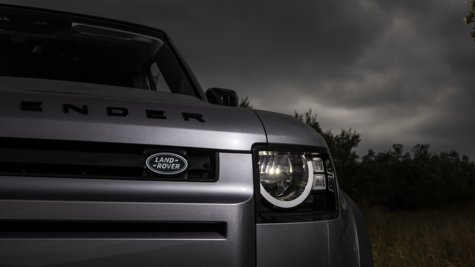 Drive Car of the Year Best Off-Road SUV 2021 finalist Land Rover Defender close-up for left headlight and badge.