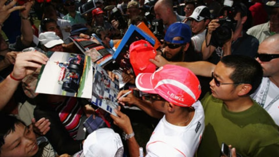Lewis Hamilton signs autographs surrounded by a throng of fans during previews for the Australian Formula One Grand Prix.