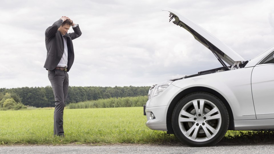Man holds his head as his car has stalled
