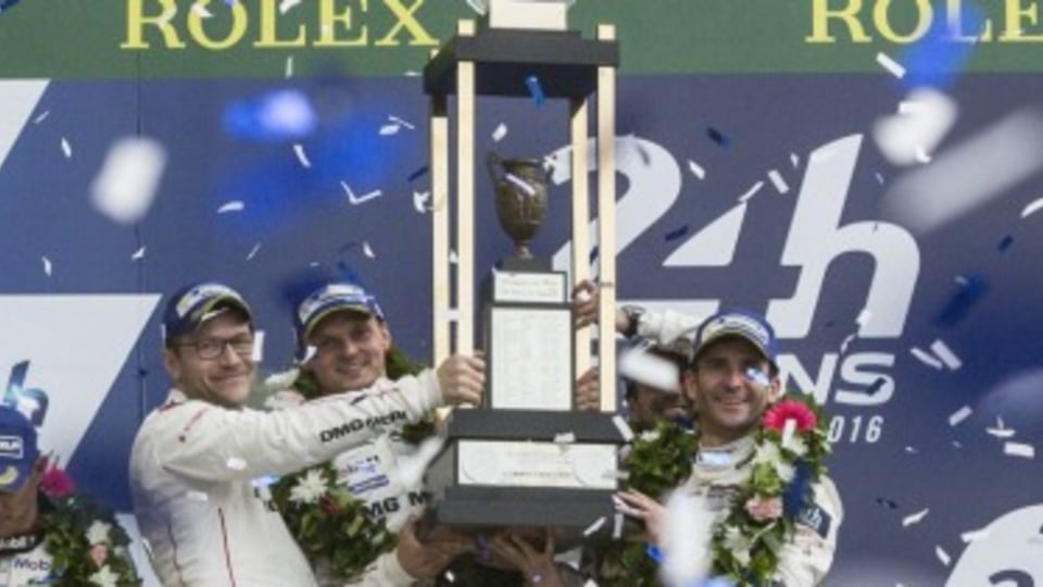 Drivers of the Porsche 919 Hybrid No2 driven by Neel Jani of Switzerland, Romain Dumas of France and Marc Lieb of German celebrate on the podium with the trophy, after winning the 84th 24-hour Le Mans endurance race, in Le Mans, western France, Sunday, Ju