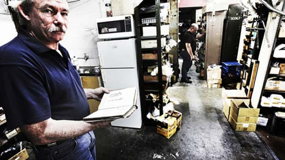Chris Ray looks at the Triumph mechanical  bible, while Preston searches for parts.