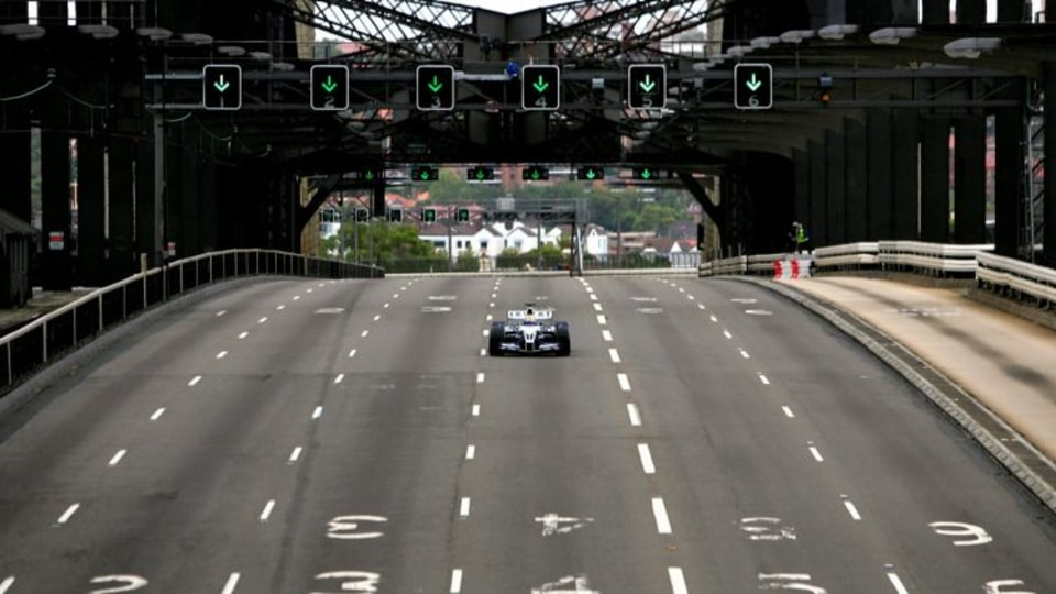Mark Webber drives his car across the Sydney Harbour Bridge in a promotional event in 2005.