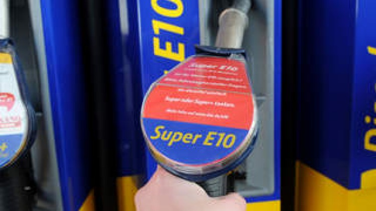A customer holds a petrol pump nozzle providing biofuel E10 in Hamburg, northern Germany, on March 4, 2011. German government seeks a solution to buoy up the sale of Super E10 biofuel at a summit with oil economy, car industry and consumer protectors.   A