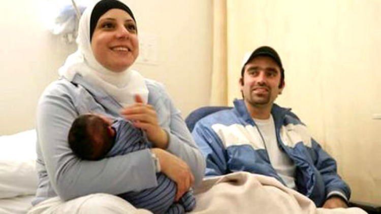 Majida Sakkal cuddles newborn son Yussef while proud husband and father Bassam looks on. Mrs Sakkal gave birth on Bulleen Road, helped by her husband, who was instructed by an emergency operator over the phone. Photo: Simon Schluter