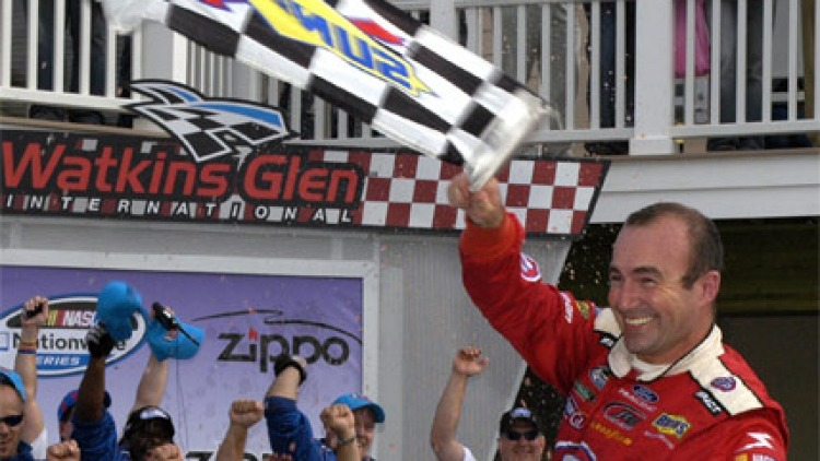Marcos Ambrose, waves the checkered flag after winning the NASCAR Nationwide Series