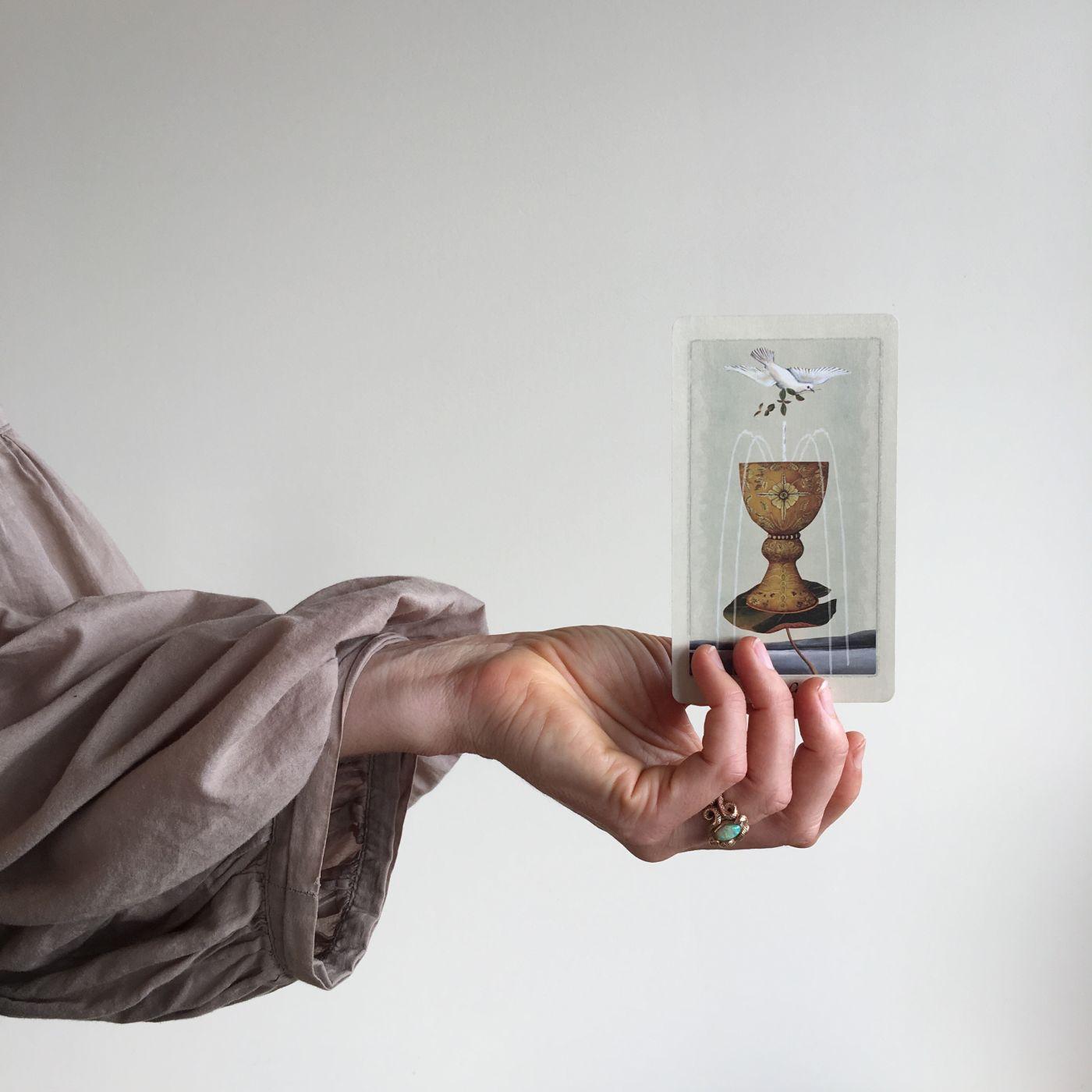 A hand holding a tarot card