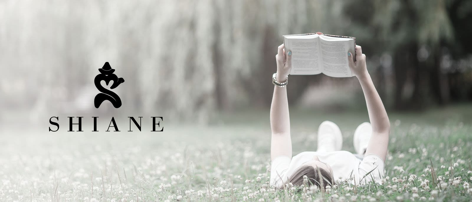 Woman reading book while laying on grass