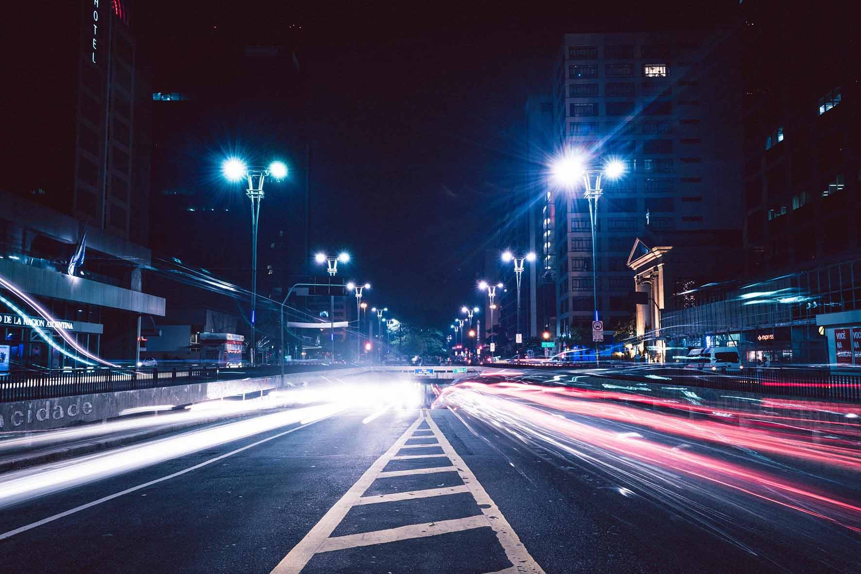 time lapse image of traffic lights streaming through a city at night with streetlights brightly shining
