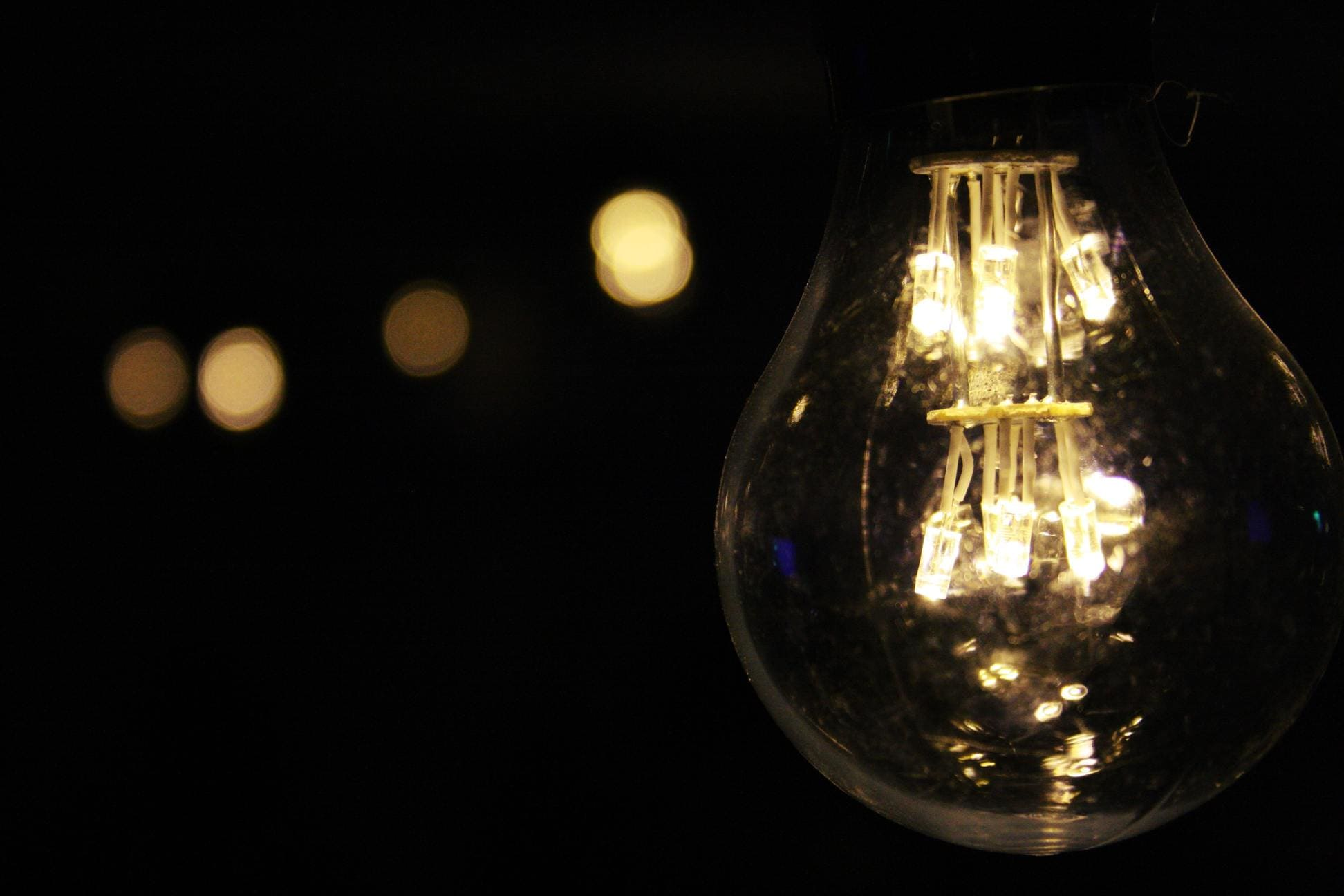 close up of a light bulb at night with blurred light behind