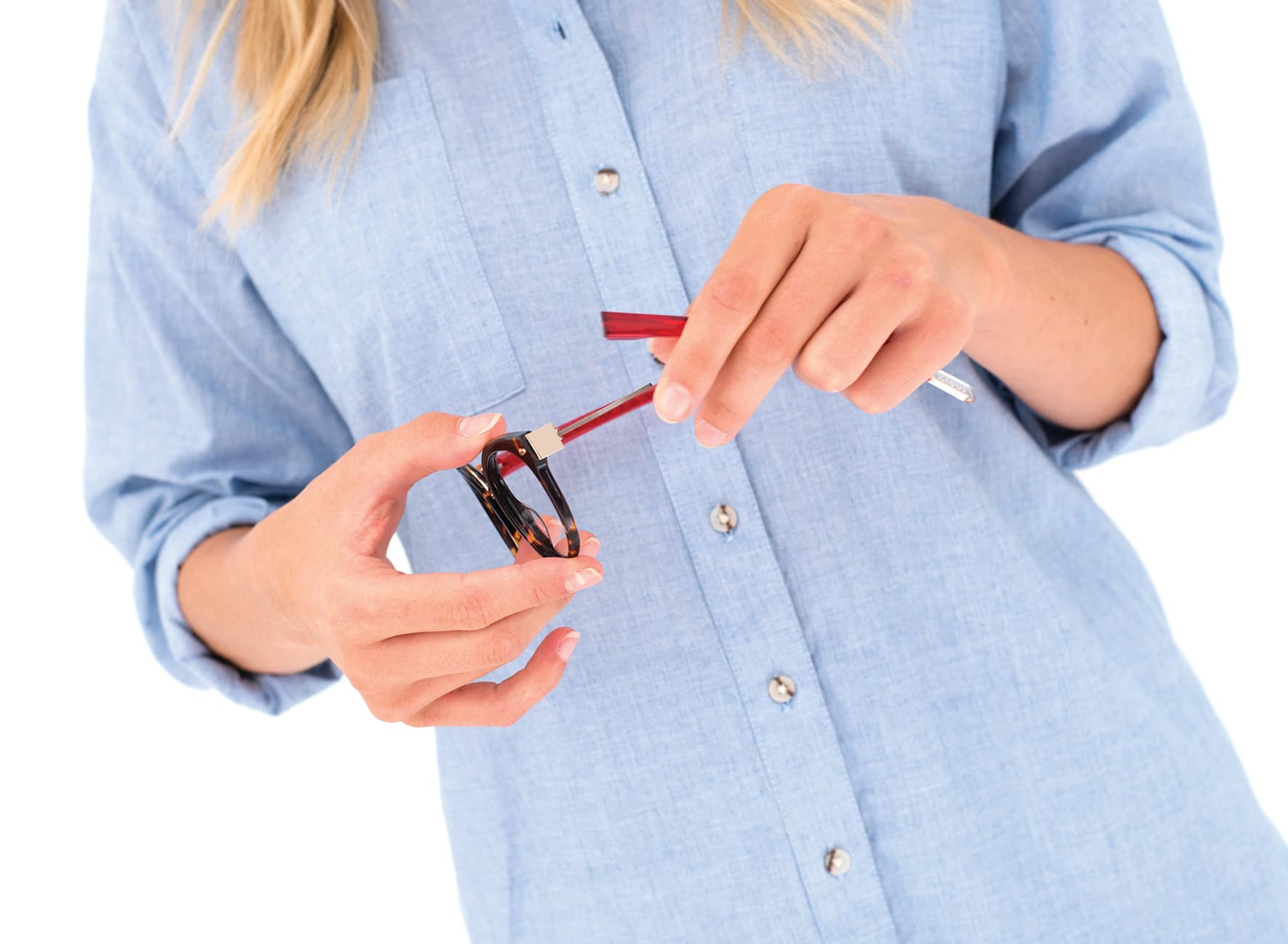 Woman in pale blue button down shirt removing a red transparent arm from a pair of round tortoiseshell acetate glasses