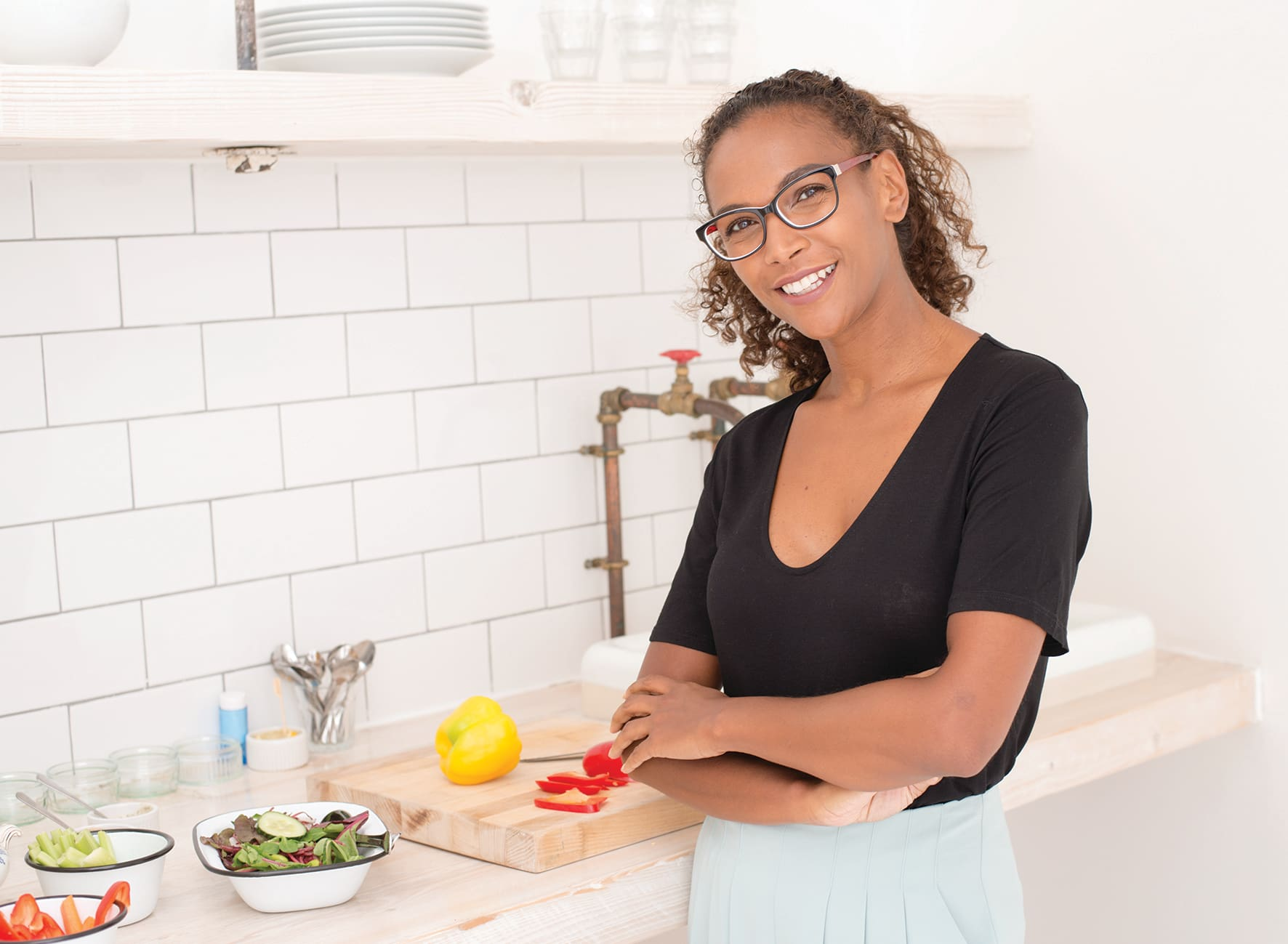 Young brown haired woman in a black t-shirt and white skirt cooking in the kitchen in front of yellow and red peppers, green lettuce and cucumber and cutting board and knife while wearing black squared glasses with brown arms