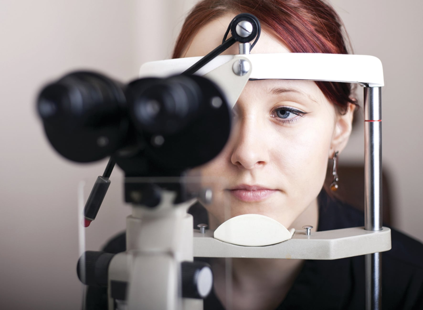 Young woman with brown hair and blue eyes having her eyes tested with her chin resting on an ophthalmometer