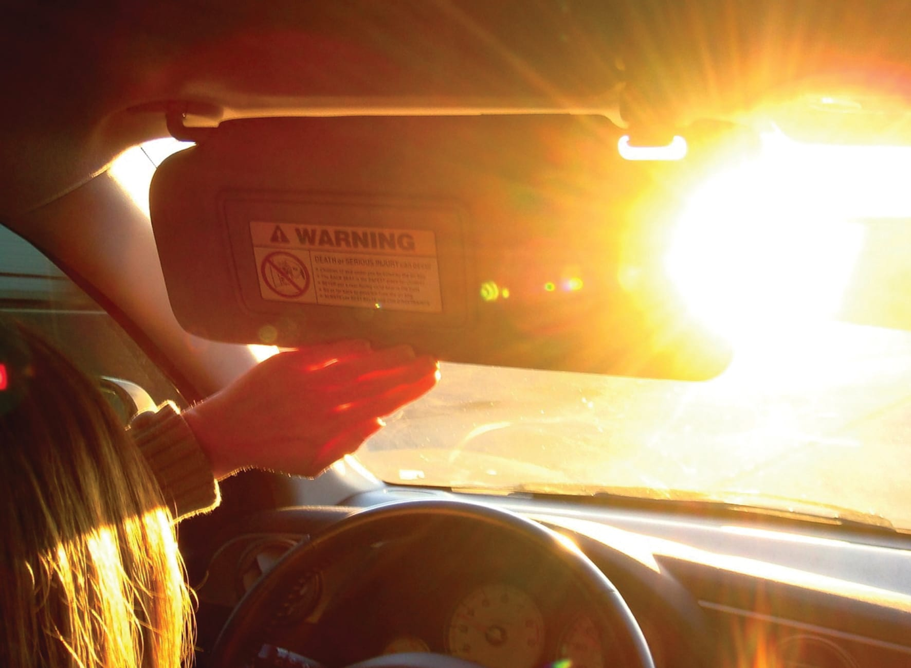 woman shielding her eyes from the sun with a car sun visor behind the wheel