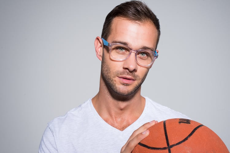 young man with stubble and short brown hair holding an orange basketball on a grey background, wearing a white t shirt and wearing transparent framed glasses with blue sides