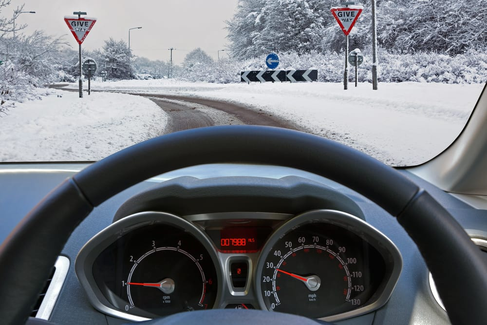 car steering wheel, dashboard, and windshield looking out onto a snowy bend with street signs