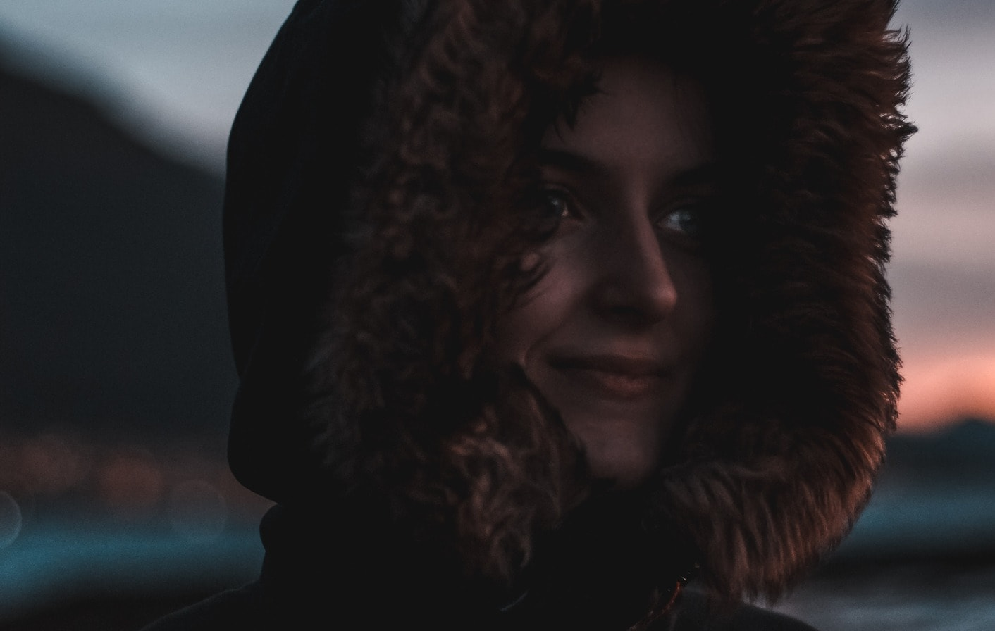 close up of a young woman smiling while wearing a parka coat with her hood up at night