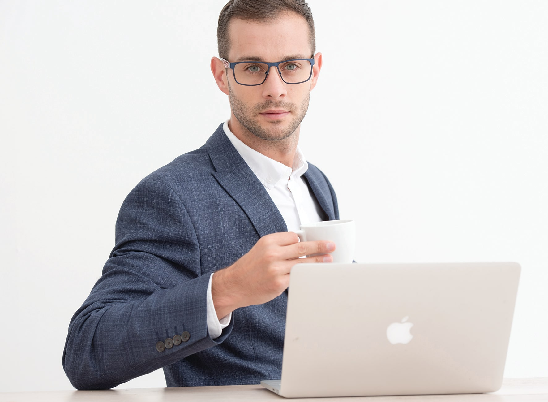 Young professional man with stubble and short brown hair sat at a Mac computer in a blue check suit and white button down shirt holding a coffee and wearing blue metal glasses with black and white contemporary pattern arms while holding a coffee