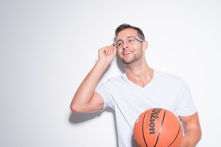 young athletic man with short brown hair and stubble wearing a plain white v-neck t-shirt and transparent framed glasses with sky blue arms while holding a basketball