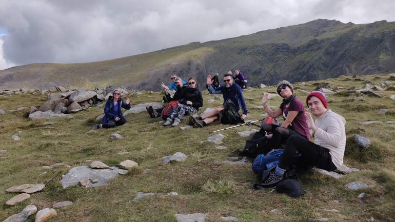 Walkers taking a short break during the ascent with the final ridge and summit in the background