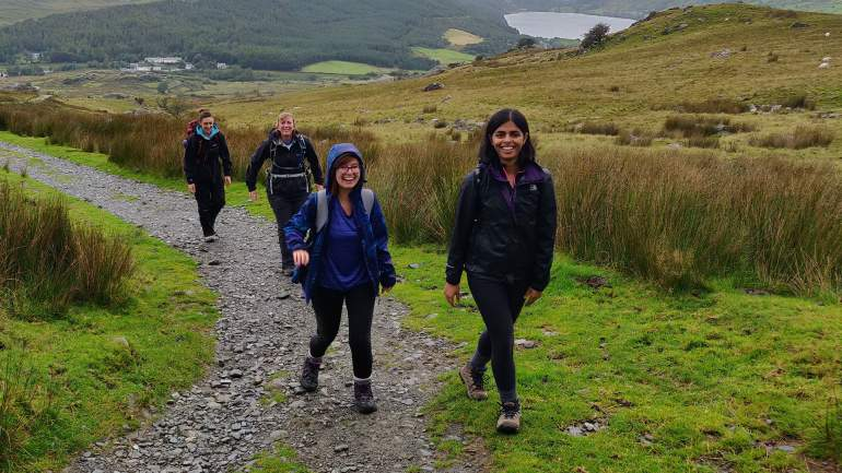 Redweb staff walking up a gravel path with hills, lake and a grey sky