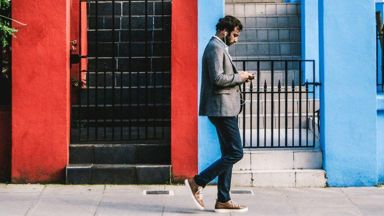Man walking down street with earphones in, looking at his phone