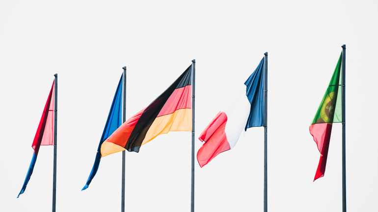 Five country flags on flagpoles
