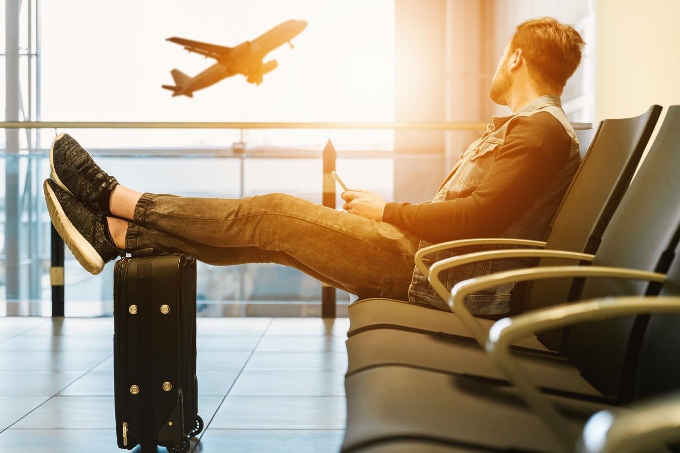 Man sat down looking at an aeroplane through a window