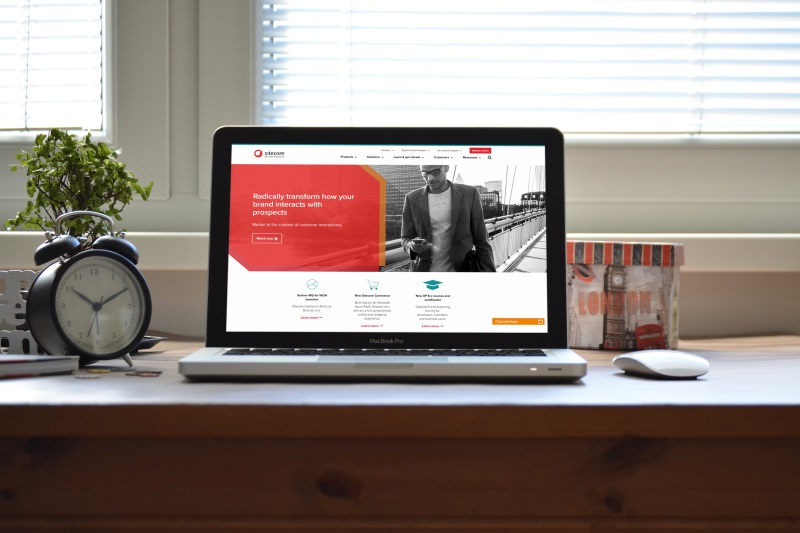 Image of a laptop on a desk displaying the Sitecore website