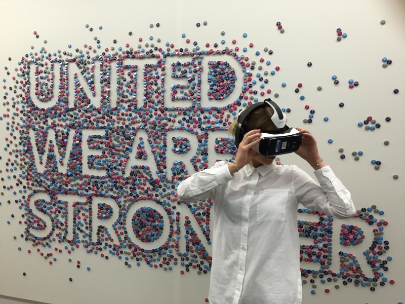 A photo of a woman wearing a VR headset stood behind a wall that reads 'United we are stronger'