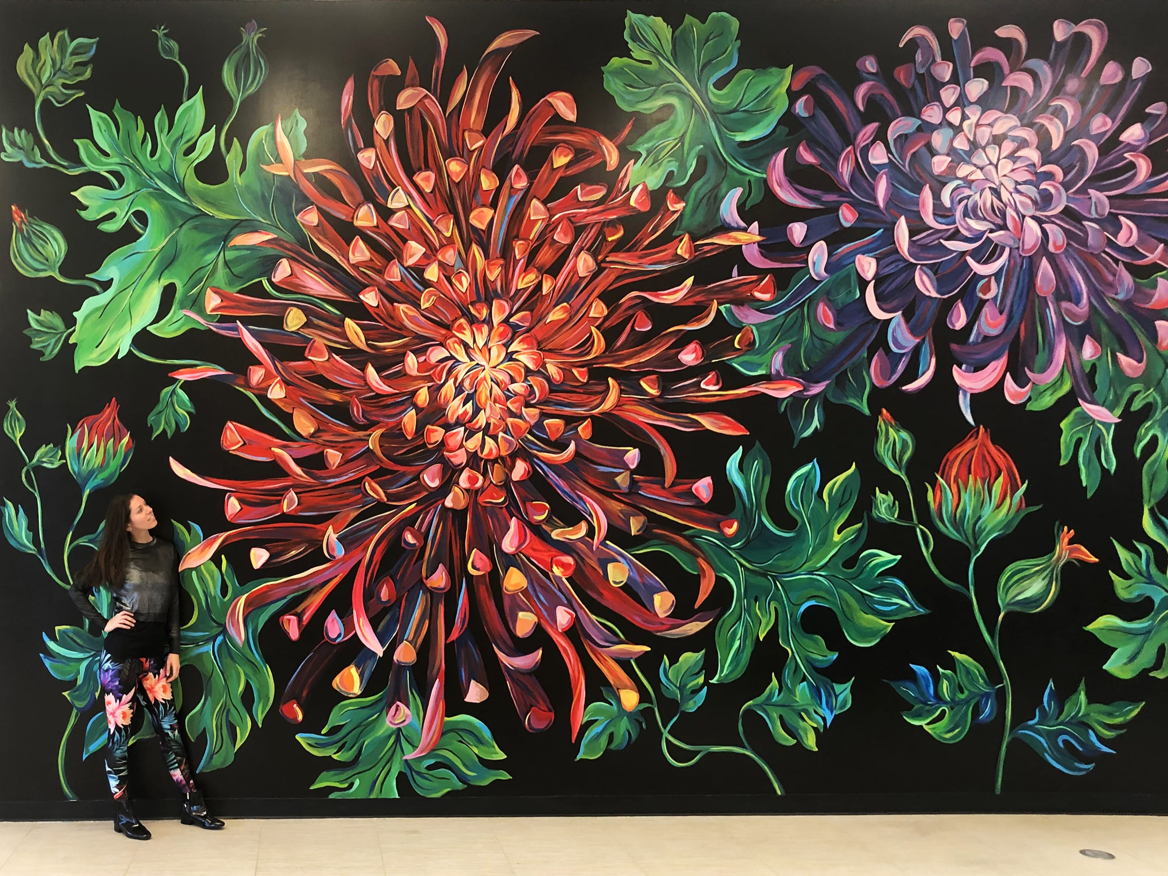 artist standing in front of painted flower mural