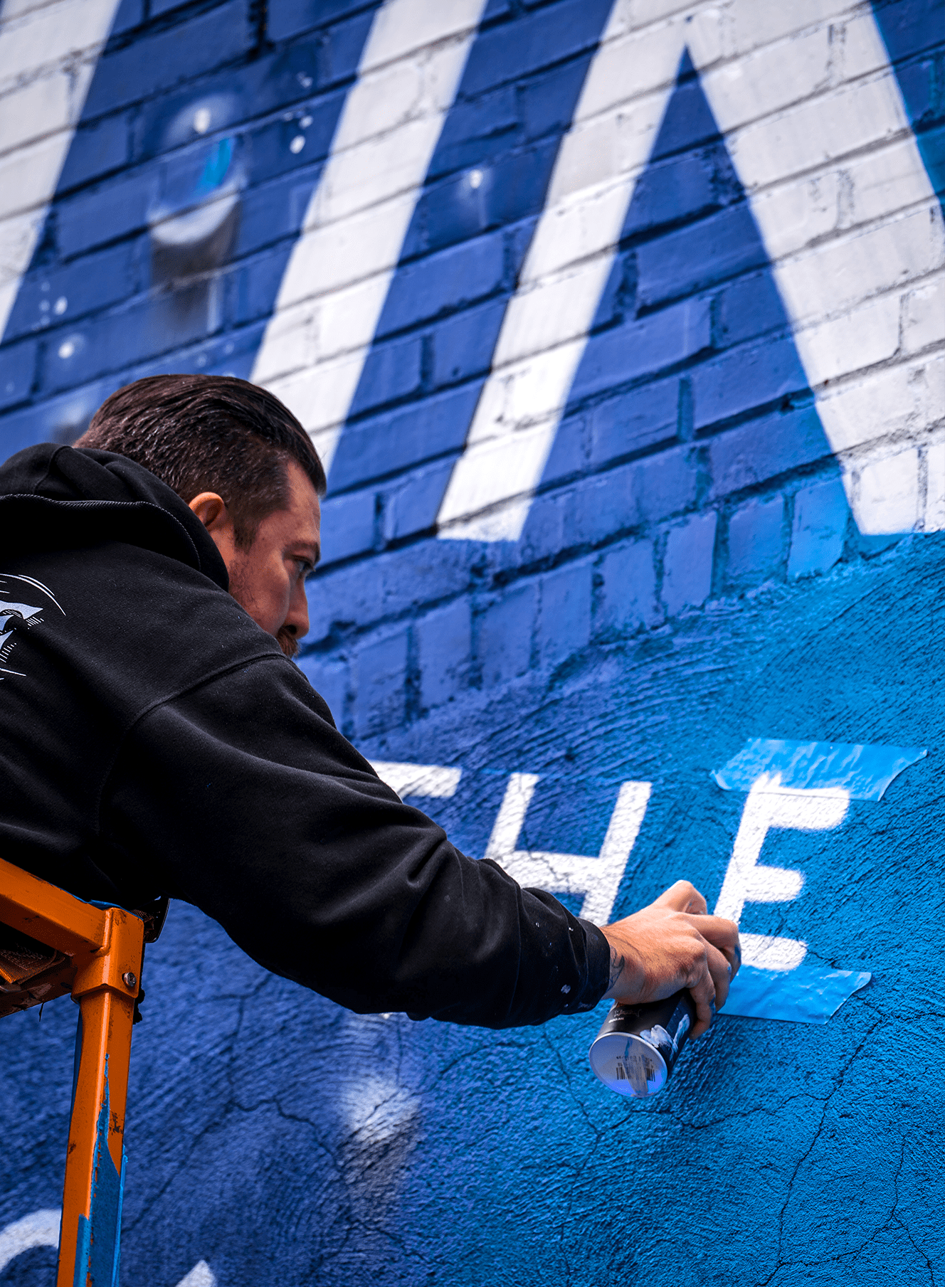 man spray painting the letter E on budlight platinum outdoor advertising mural