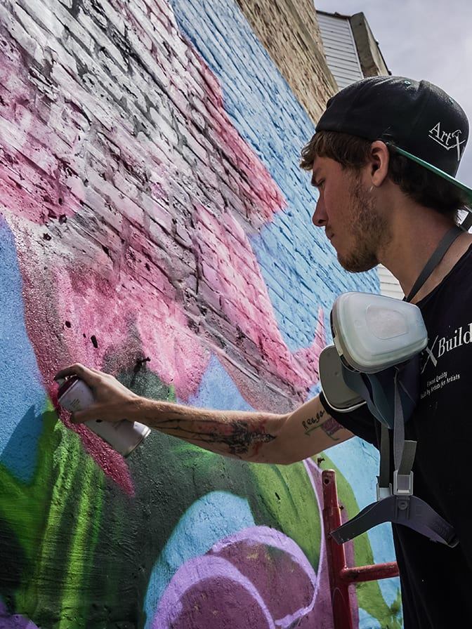close up of artist spray painting pink flowers on the side of a building for an outdoor mural