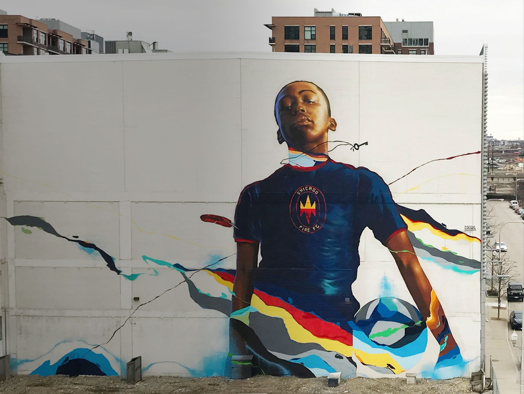 outdoor mural on the side of a building of kid wearing a Chicago Fire soccer jersey