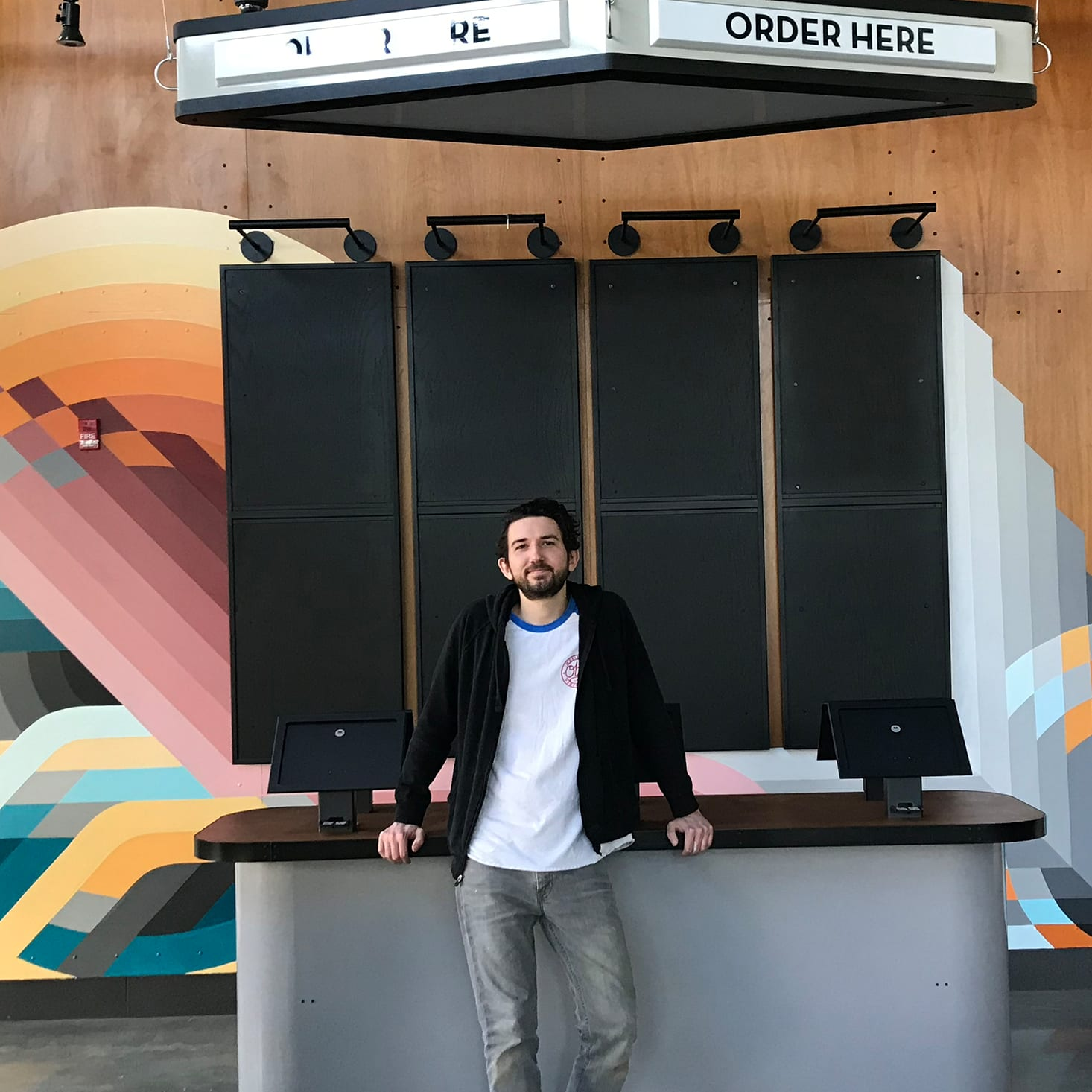 artist standing in front of shake shack wall mural