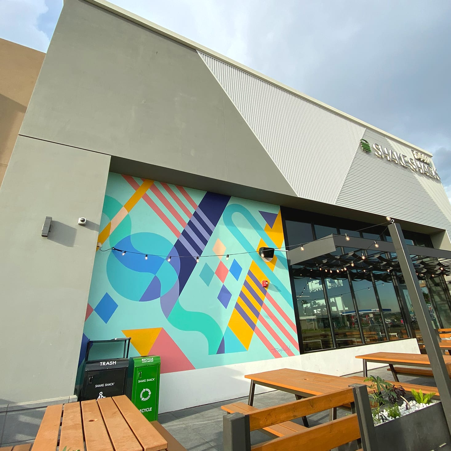 exterior mural on a shake shack restaurant in long beach california with bright colors and abstract shapes