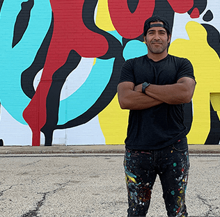 artist standing with arms folded in front of a building mural he just painted