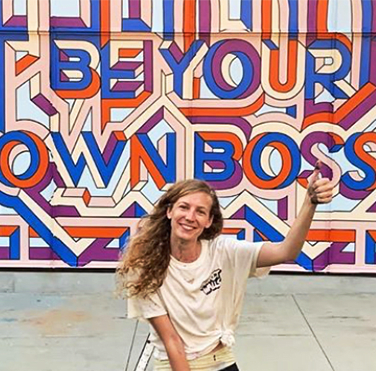 female artist sitting in front of a mural she painted that reads be your own boss