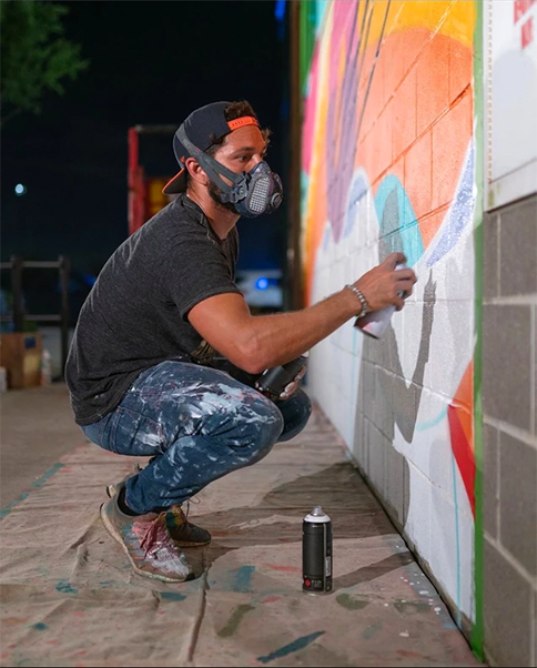 artist wearing a mask while he paints a mural on the side of a building