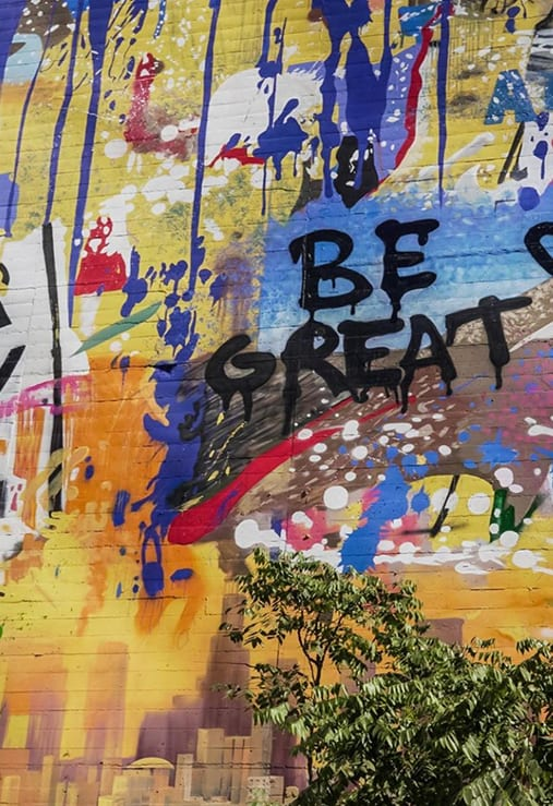 close up of graffiti art on a wall that says Be Great
