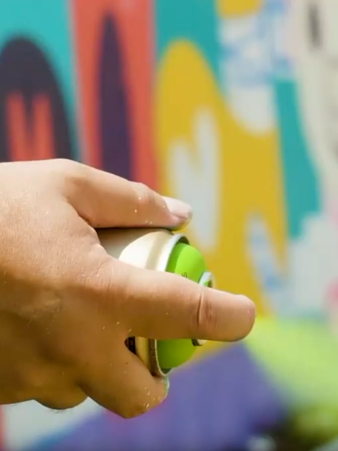 close up of hand spraying green spray paint with a mural in the background