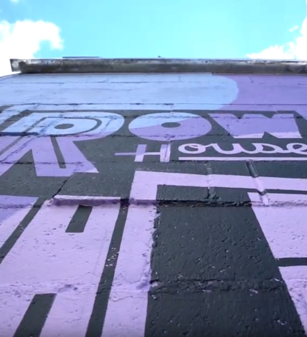 shot from the ground looking up at the sky along building-side mural that is black and purple